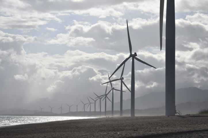 windmills on seashore under white clouds